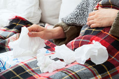Runny nose. Person having a runny nose, sitting under blanket Stock Images