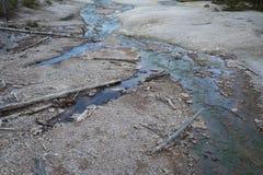 Runoff för blått vatten från en geyserpöl i den Yellowstone nationalparken Royaltyfri Bild