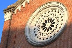 Runt fönster på väggen för röd tegelsten i italiensk arkitektur fotografering för bildbyråer