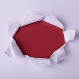 Runt hål i papper med röd bakgrund inom Arkivfoton