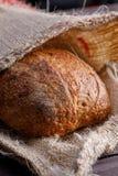 Runt hantverkarerågbröd i en påse Stilleben på träbakgrund fotografering för bildbyråer