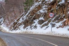 Runt hastighetsbegränsningvägmärke på bergvägen Royaltyfri Foto