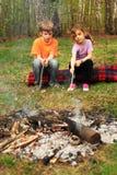 runt om campfire sitter barn två arkivbild