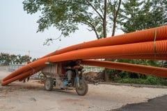 Runt om Kina - man på trehjulingen som överlastas med 20m långa rör Arkivbilder