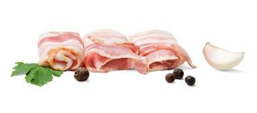 Runt rånar av bacon med kryddor på en vit bakgrund arkivbilder