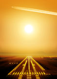 Runway. Passenger plane fly up over runway from airport at sunset Stock Photography