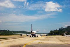 Runway with an aircraft. A runway with taking off aircraft. of Phuket airport, island of Thailand Stock Photos