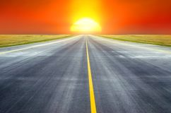 Runway at the airport the horizon at sunset in the center of the sun. Runway at the airport the horizon at sunset in the center of the sun Stock Image