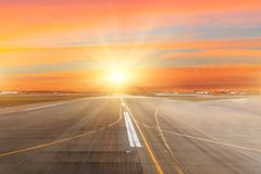 Runway at the airport the horizon at sunset in the center of the sun light rays. Runway at the airport the horizon at sunset in the center of the sun light rays Royalty Free Stock Photo