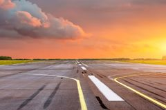 Runway at the airport the horizon at sunset in the center of the sun. Runway at the airport the horizon at sunset in the center of the sun Royalty Free Stock Image