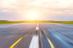 Runway at the airport in the morning at dawn sunset sun light motion blur. Runway at the airport in the morning at dawn sunset sun light motion blur Stock Photo