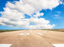 Runway, airstrip in the airport terminal with marking on blue sky with clouds background. Travel aviation concept... Runway, airstrip in the airport terminal Royalty Free Stock Photos