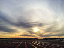 Runway. With hazy sky at sunset, a plane flying over and other planes on the ground Royalty Free Stock Photography