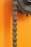 Ruota dentata e catena nere del metallo su fondo arancio Fotografia Stock Libera da Diritti