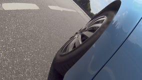 Ruota di automobile blu che supera il dosso stradale, controllo di ostacolo, viaggio dell'automobile sulla carreggiata archivi video