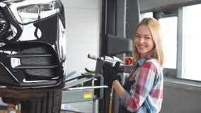 Ruota di automobile d'avvitamento della ragazza bionda al garage stock footage