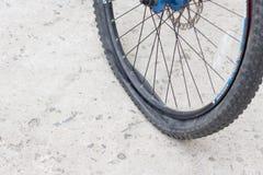 Ruota di bicicletta con la gomma a terra sulla strada cementata Fotografie Stock
