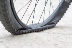 Ruota di bicicletta con la gomma a terra sulla strada cementata Immagini Stock Libere da Diritti
