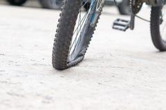 Ruota di bicicletta con la gomma a terra sulla strada cementata Fotografie Stock Libere da Diritti