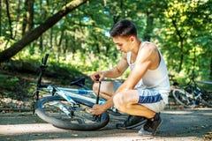 Ruota di pompaggio dell'uomo di una bicicletta Il concetto di riciclaggio e di un hea Fotografie Stock Libere da Diritti