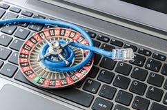 Ruota di roulette e cavo di lan che si trova sulla tastiera di computer che simbolizza crittografia di dati fotografie stock