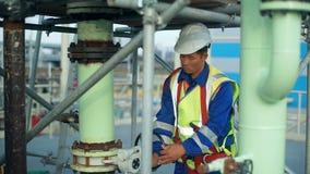 Ruota girante del lavoratore asiatico alla grande raffineria di petrolio stock footage
