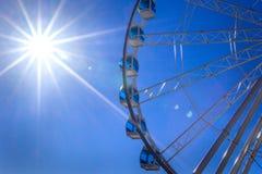 Ruota panoramica bianca con le cabine blu-chiaro di vetro contro il cielo blu ed il sole con i raggi luminosi, Helsinki, Finlandi Fotografie Stock Libere da Diritti