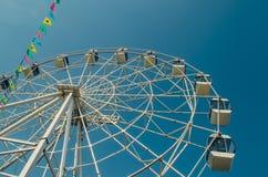 Ruota panoramica e bandiere variopinte nel parco di divertimenti contro Th fotografia stock