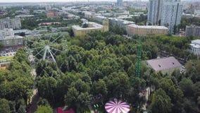 Ruota panoramica e montagne russe in un parco di divertimenti, vista superiore clip Vista superiore della città con la ruota pano video d archivio