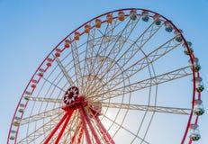 Ruota panoramica su un fondo di chiari cielo blu e sole Fotografie Stock Libere da Diritti