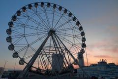 Ruota panoramica vicino al complesso di acquisto e di spettacolo di Gorki al tramonto immagine stock libera da diritti