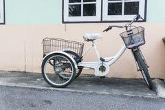 Ruote della bicicletta tre che parcheggiano a casa Fotografie Stock Libere da Diritti