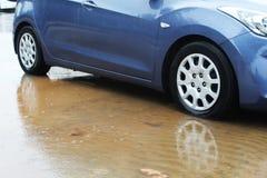 Ruote di automobile dentro una pozza di acqua piovana, delle gocce di pioggia e dei cerchi dell'acqua Tempo di inverno in Israele fotografia stock
