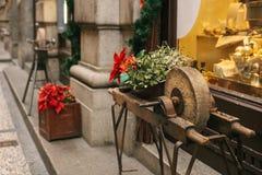 Ruote di pietra antiche sulle strutture di legno decorate con i fiori rossi all'entrata al deposito con il Natale Fotografia Stock Libera da Diritti