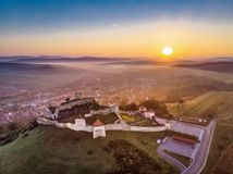 Rupea Fortress in Transylvania, Romania icon and one of the most visited tourist attractions. Aerial Romania landscape shot using a drone at sunrise royalty free stock photos