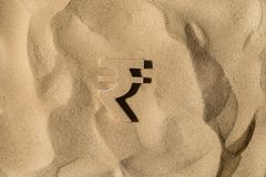 Rupee Symbol Under the Sand. Indian Rupee Symbol or Sign Covered with Sand in the Sun after Crisis stock image