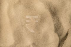 Rupee Symbol Under the Sand. Indian Rupee Symbol or Sign Covered with Sand in the Sun after Crisis royalty free stock photo