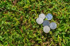 Rupiah coin money on green grass. Multiple hundred Indonesia Rupiah coin money on green grass background Stock Image