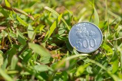 Rupiah coin money on green grass. Single five hundred Indonesia Rupiah coin money on green grass Stock Photography