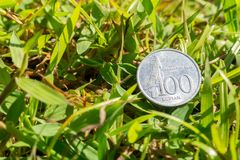 Rupiah coin money on green grass. Single hundred Indonesia Rupiah coin money on green grass background Royalty Free Stock Image