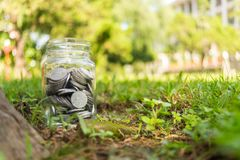 Rupiah Coin Money in jar on Green Grass Nature Background. Rupiah Coin Money in jar bottle on Green Grass Nature Background Stock Photos