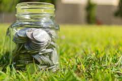 Rupiah Coin Money in jar on Green Grass Nature Background. Rupiah Coin Money in bottle jar on Green Grass Nature Background Royalty Free Stock Image