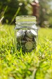 Rupiah Coin Money in jar on Green Grass Nature Background. Rupiah Coin Money in jar bottle on Green Grass Nature Background Stock Photography