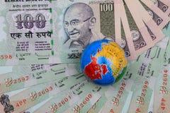 Rupias indianas da moeda com um globo Fotografia de Stock Royalty Free