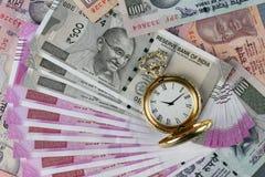 Rupias indianas novas da moeda com o relógio antigo do tempo
