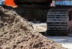 rupsbandgraafwerktuig en een stapel van zand op bouwconstructieplaats aan reparatieweg Stock Foto