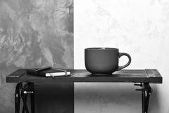 Ruptura de café e conceito produtivo do dia Café quente na tabela preta no interior moderno Diário com pena e copo dentro fotografia de stock royalty free