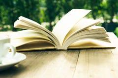 Ruptura de café e livro aberto na tabela de madeira fotos de stock