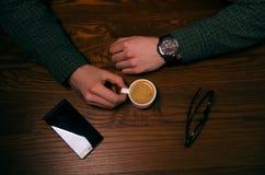 Ruptura de café A mão do homem mantém uma xícara de café em uma tabela de madeira Telefone e vidros Situação de negócio foto de stock royalty free