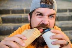 Ruptura livre do homem farpado da fome e da sede que come o cachorro quente e o café para a ruptura do petisco Indivíduo caucasia imagem de stock